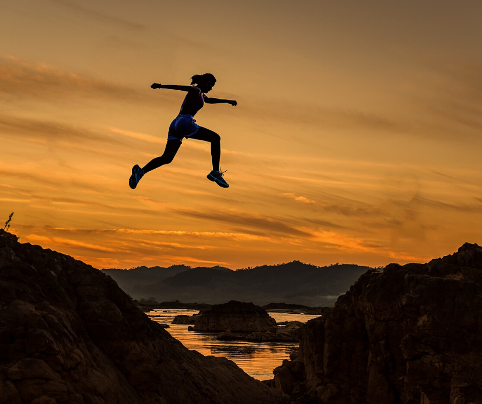 Woman leaping across a mountain